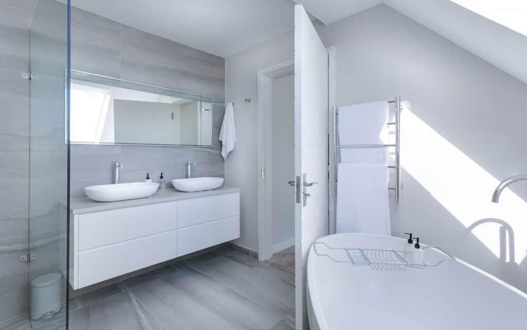 Na foto um banheiro branco com detalhes em cinza, possuindo duas pias, uma banheira e um box.