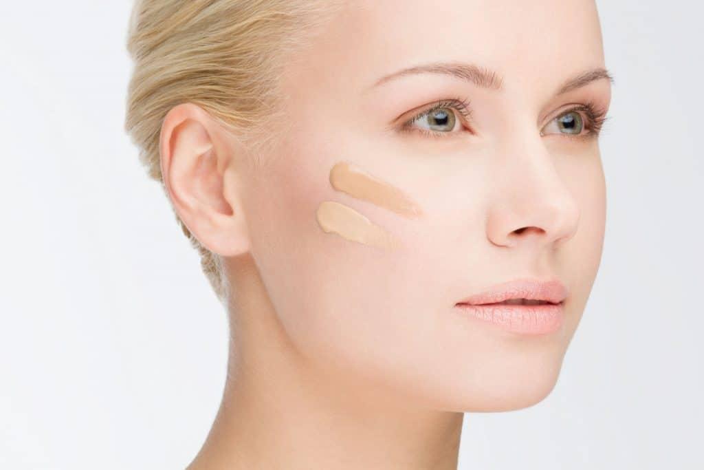 Foto que foca no rosto de uma mulher loira, de olhos claros, com o olhar longe e dois tons diferentes de base em sua bochecha.
