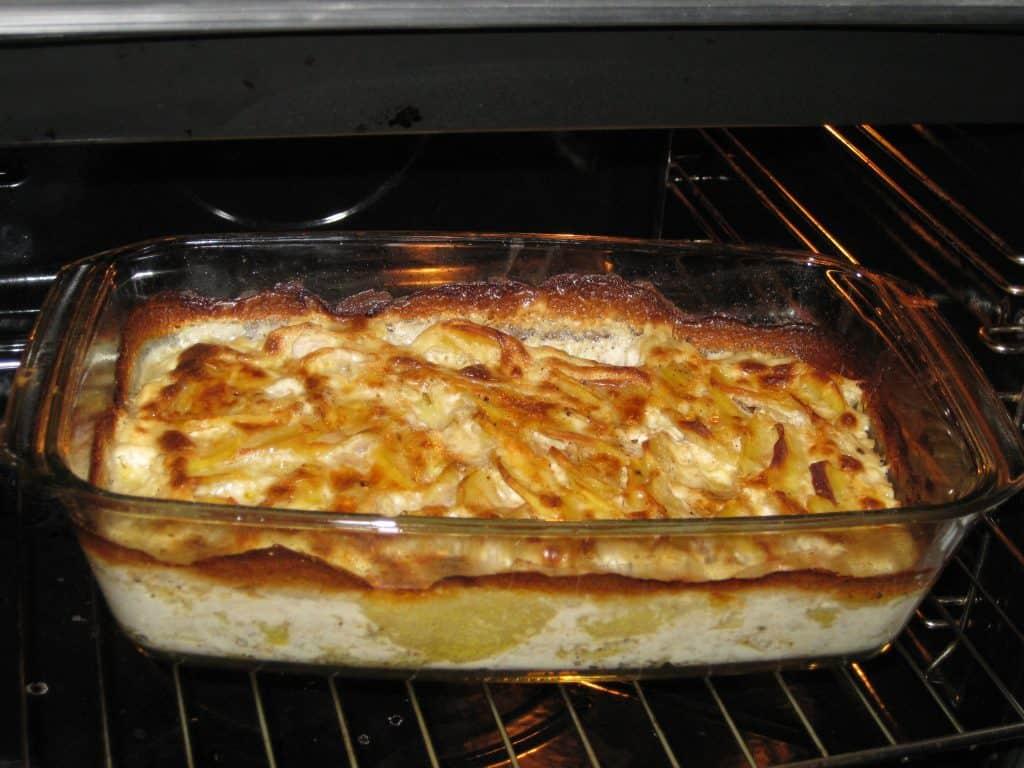 Imagem mostra um prato de batatas gratinadas no forno.