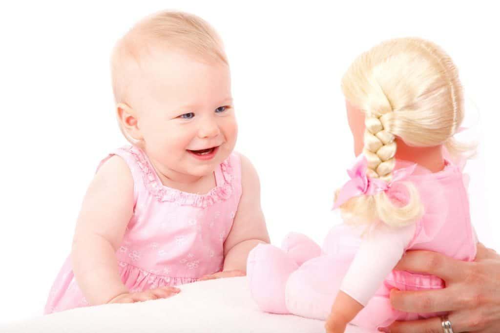 Bebê interagindo com boneca.