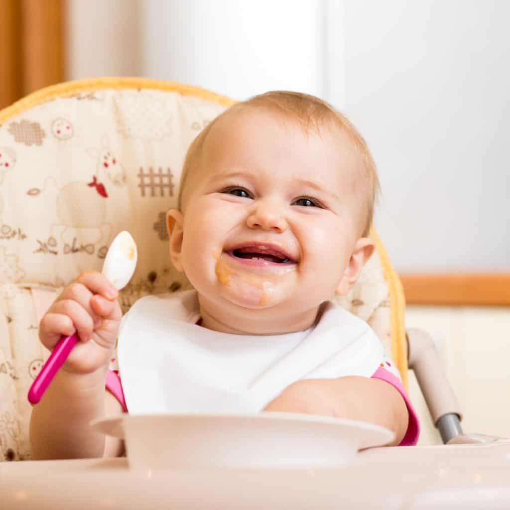 Imagem de uma bebê sentada na cadeirinha de alimentação com a boca suja segurando uma colher de plástico rosa e sorrindo.