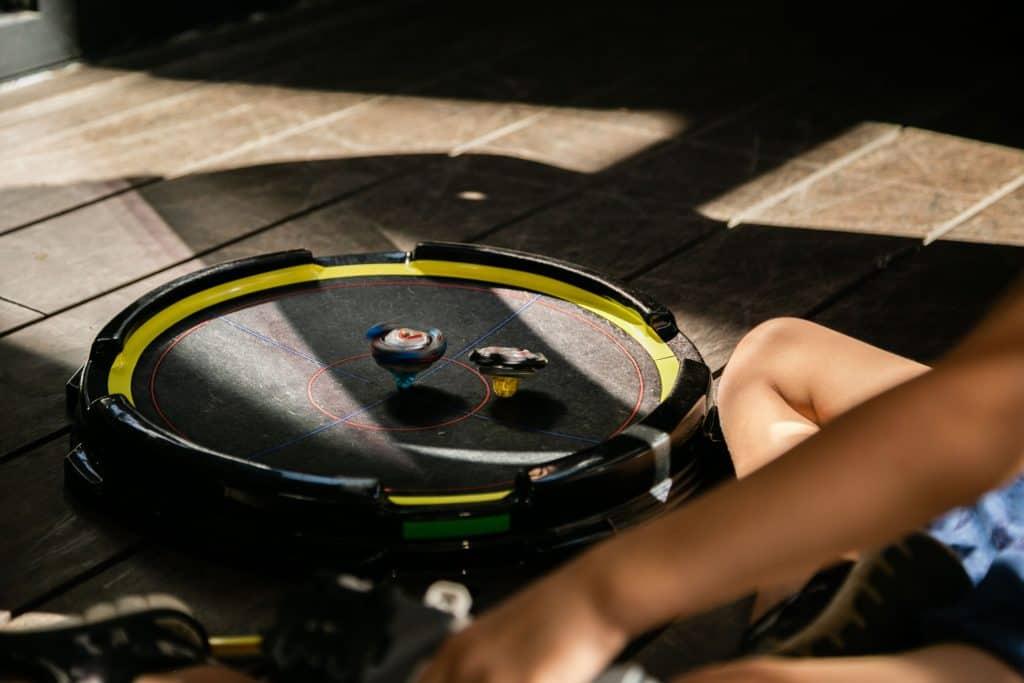 Uma criança jogando 2 piões de Beyblade em uma arena da geração 1.