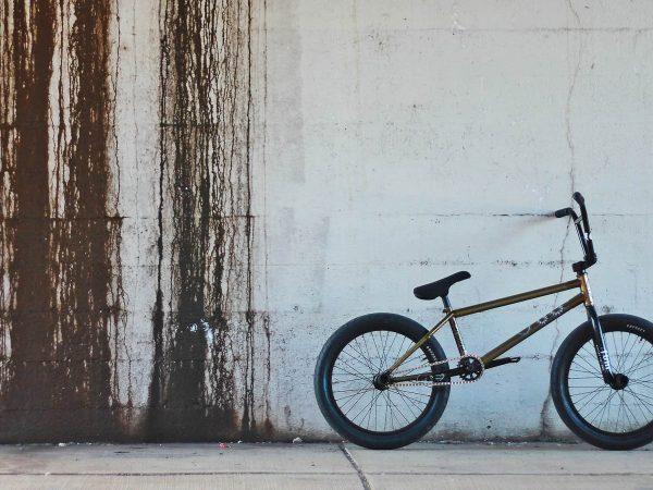 Na foto está uma bicicleta BMX em frente e uma parede branca.