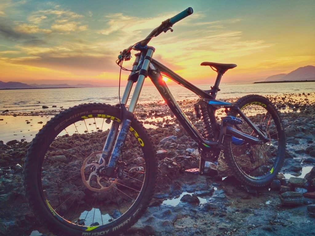 Imagem mostra uma mountain bike estacionada num terreno rochoso, na beira de uma praia, na luz do fim de tarde.