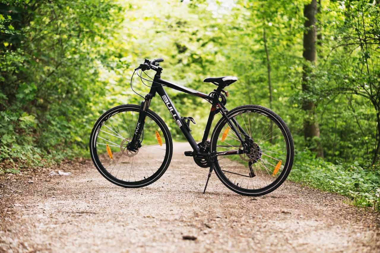Imagem mostra uma mountain bike estacionada em meio à uma trilha.