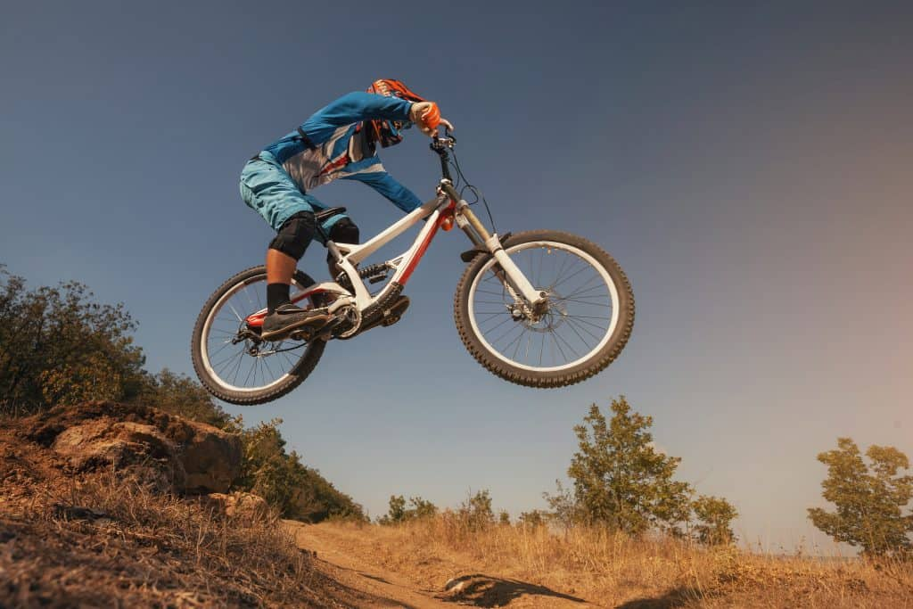 Imagem mostra um rapaz controlando sua mountain bike durante um salto.