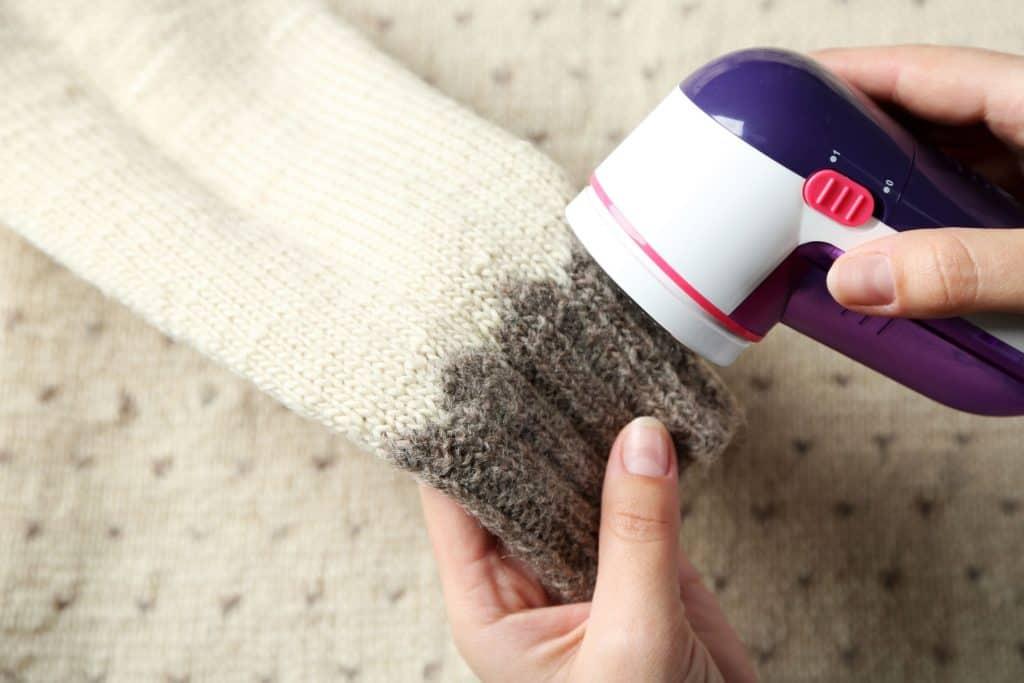 Imagem de uma mão passando um papa bolinhas elétrico em uma blusa de lã.