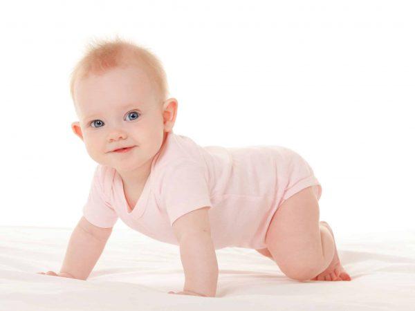 Imagem de bebê em cima de cama com body rosa.