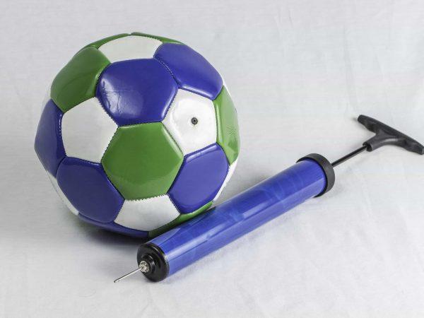 Imagem mostra uma bomba de encher bola simples, com a câmara azul, ao lado de uma bola de futebol, de gomos coloridos.