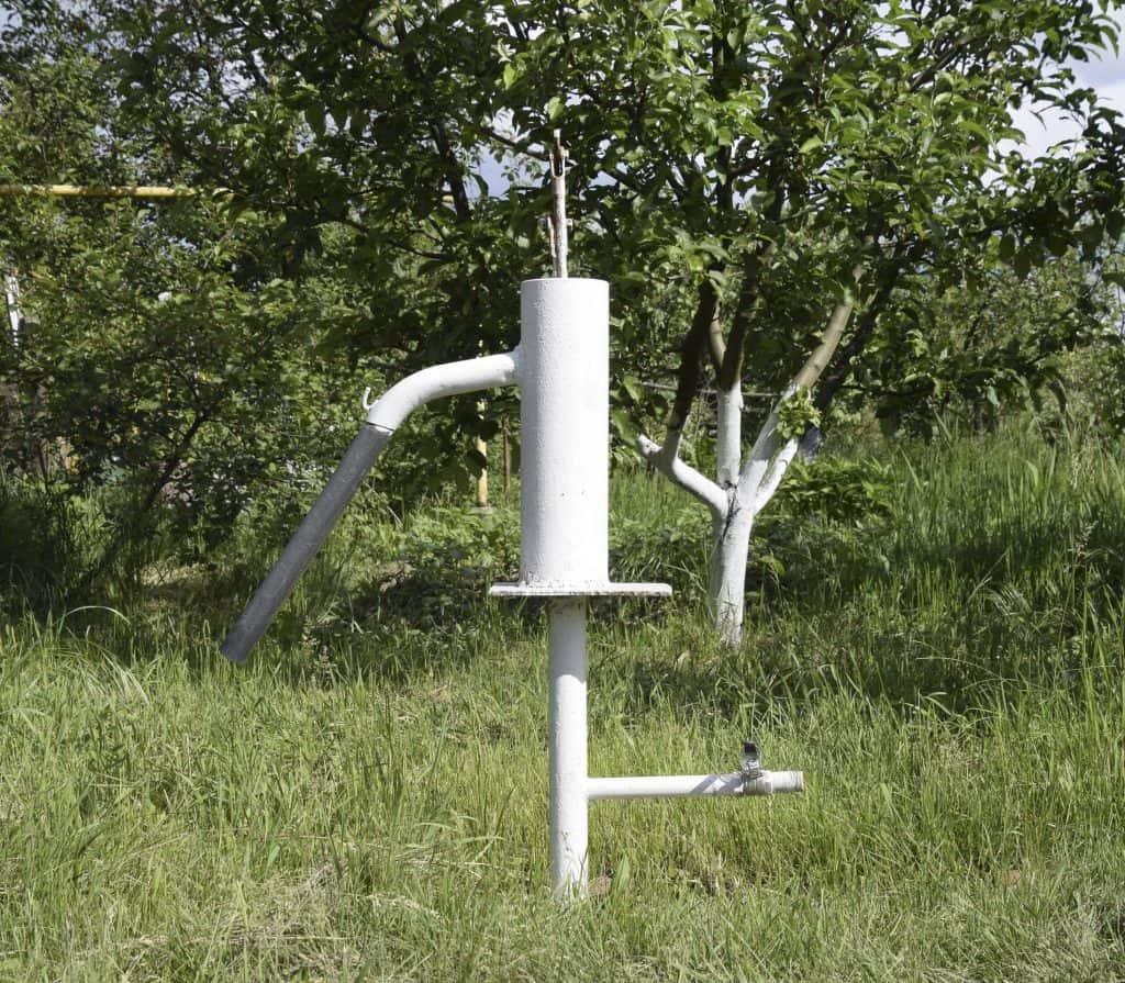 Imagem mostra poço artesiano no meio de uma gramado e perto de árvores.