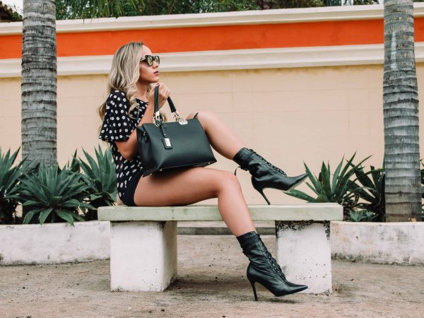 Imagem de mulher sentada em banco com botas pretas de cano médio.