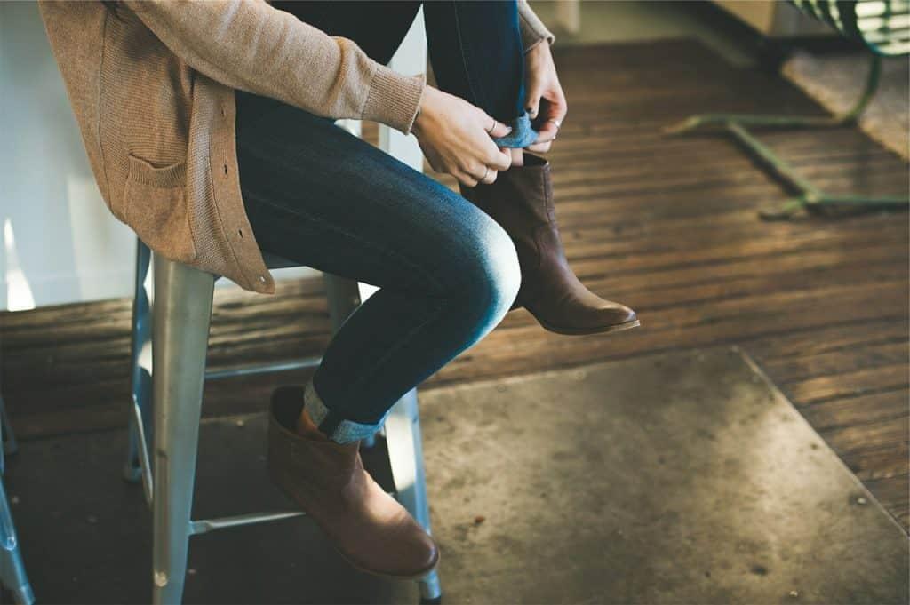 Foto que mostra mulher sentada em um banco arrumando a barra da calça jeans.