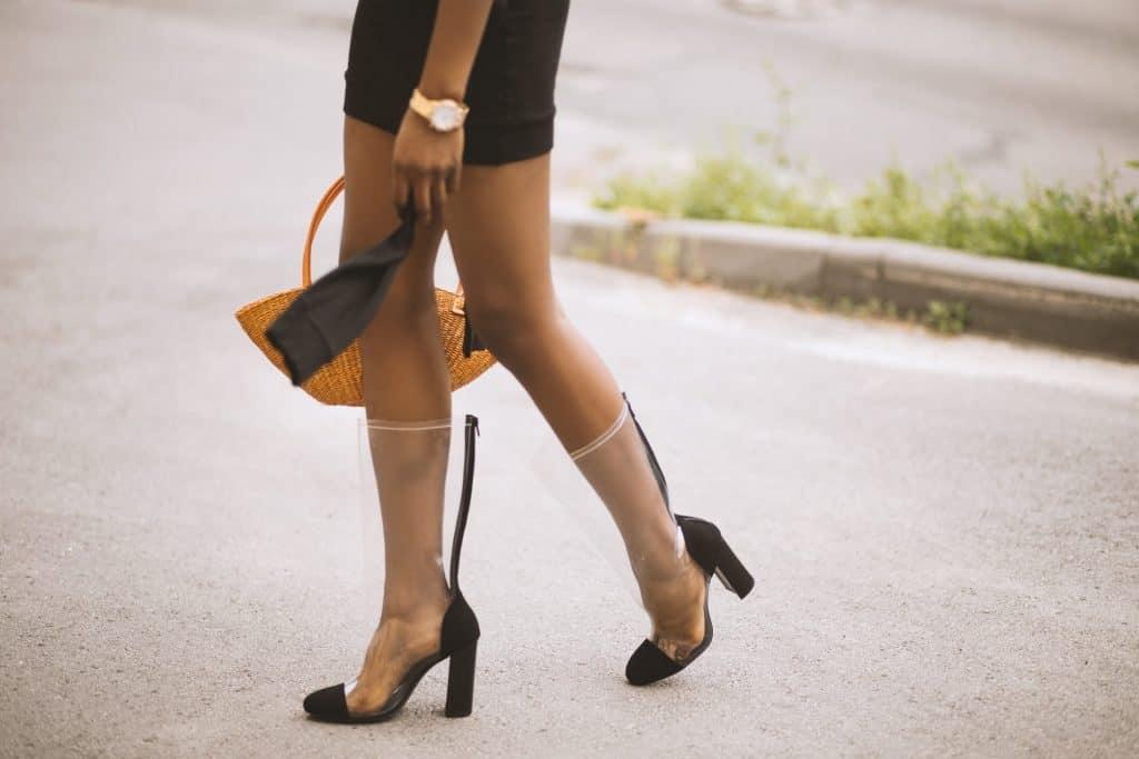 Foto que mostra as pernas e o pé de uma mulher andando, utilizando saia, relógio dourado, bolsa alaranjada e bota de cano alto transparente com detalhes em preto.