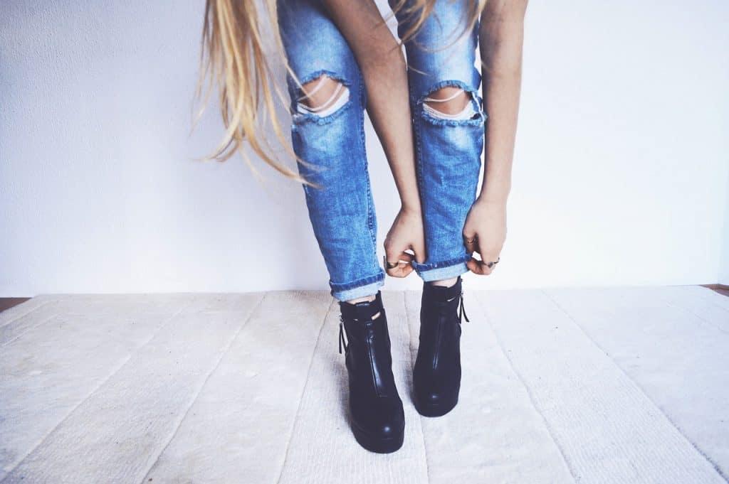 Foto que mostra mulher sentada arrumando a barra da calça jeans.