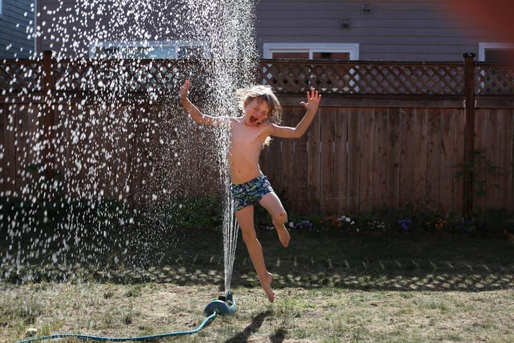 Menino brinca com a água esguichada por uma mangueira no jardim de uma casa.
