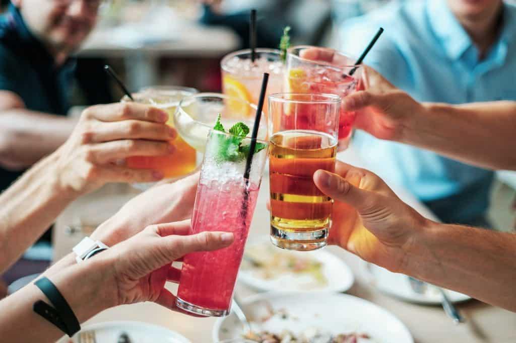 Imagem de um brinde com várias pessoas segurando bebidas diferentes em cor e formato de copos.