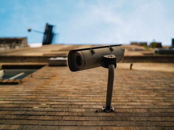 Câmera de vigilância pregada na parede.