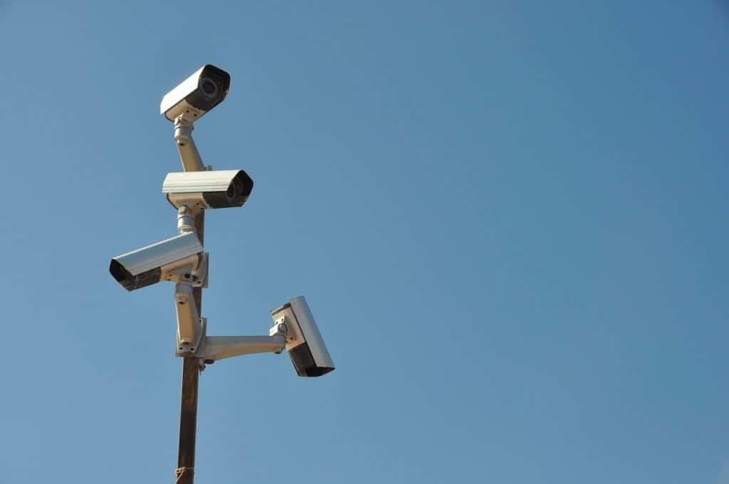 Imagem de quatro câmeras de vigilância em poste.