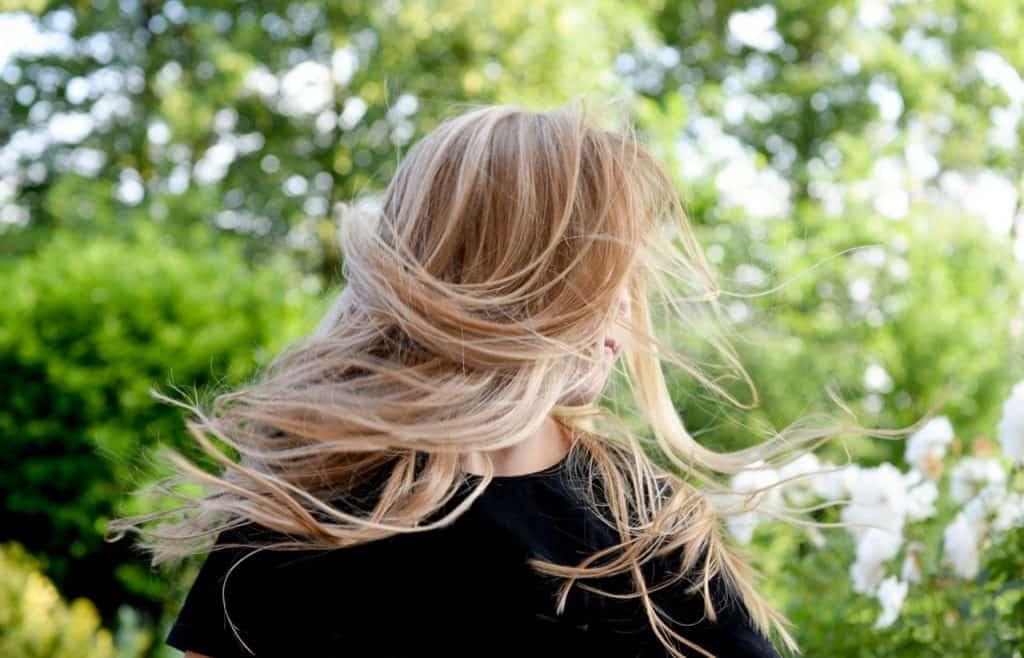 Foto de uma mulher loira, balançando os cabelos, em um local ao ar livre, com várias árvores.