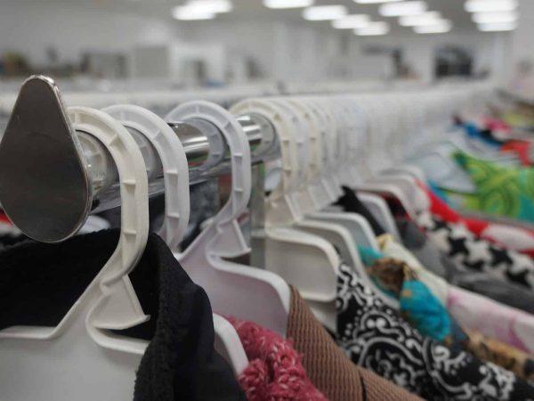 Diversos cabides de plástico com roupas penduradas e enfileiradas.