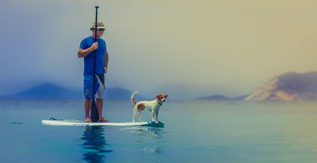 Imagem mostra um senhor e seu cachorro navegando com seu stand up inflável em uma água calma.