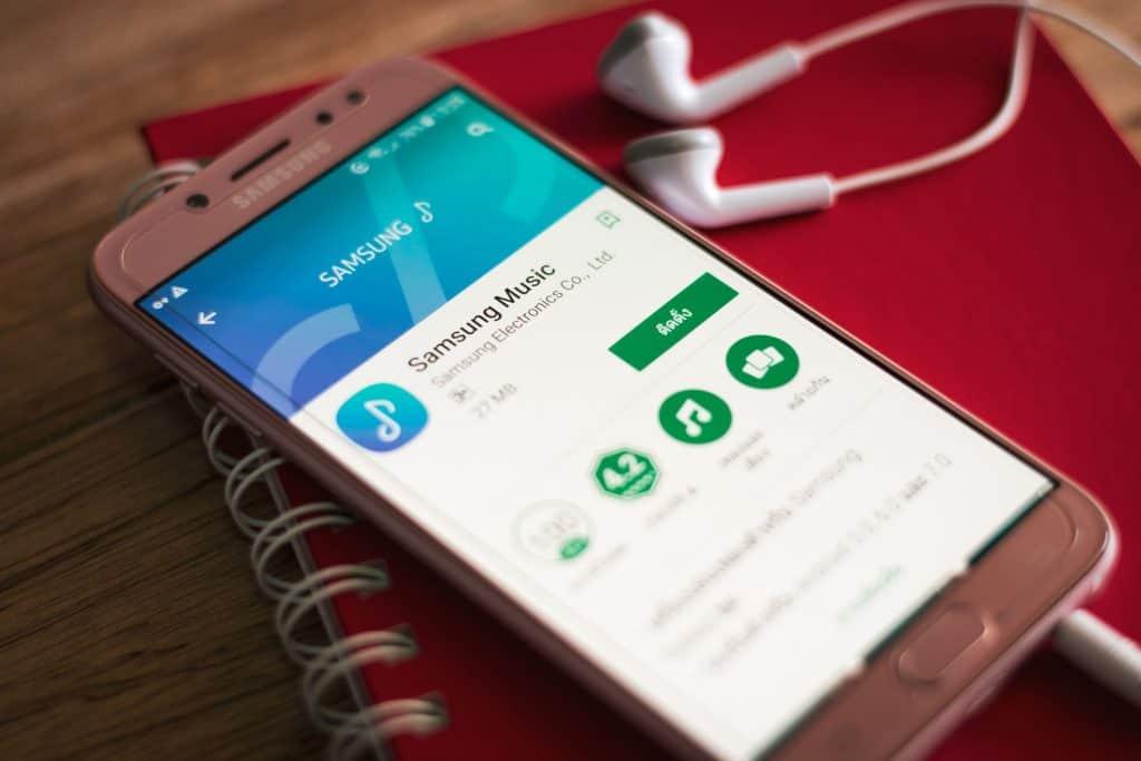 Imagem de celular com fone de ouvidos Samsung sobre um caderno de anotações vermelho.