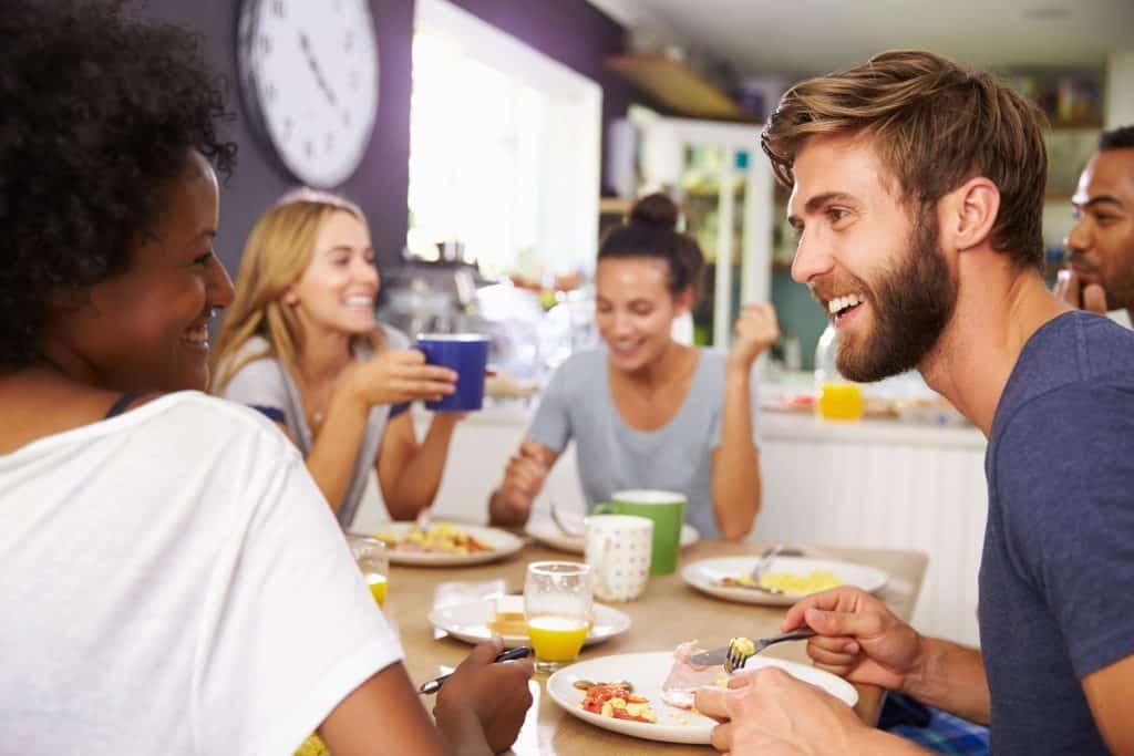 Imagem de um grupo de amigos preparando o café da manhã.