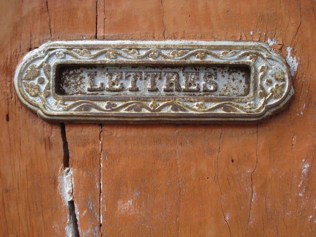 Caixa de correio antiga de bronze em uma parede.
