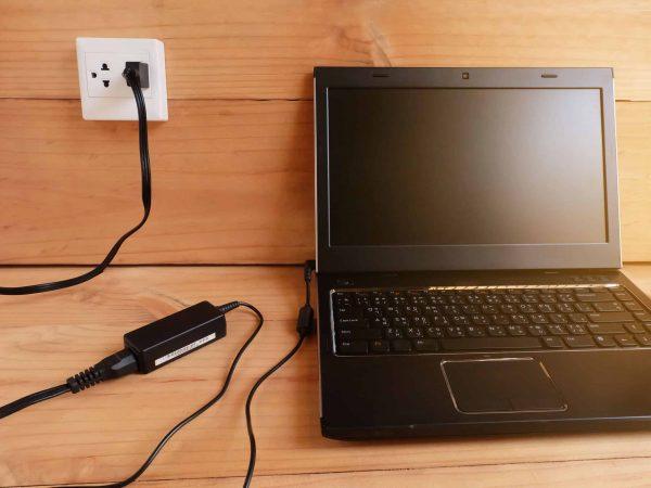Imagem mostra um laptop conectado a um carregador na tomada.