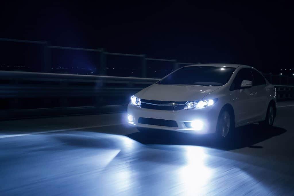 Imagem de carro na estrada com faróis de lâmpada xenon.