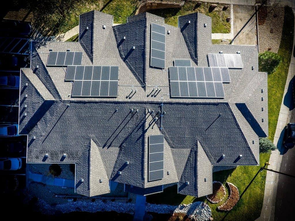 Imagem de um telhado, em uma grande construção, com painéis solares colocadas em diversos locais, proporcionando melhor aproveitamento dos raios de sol ao longo dos dias.
