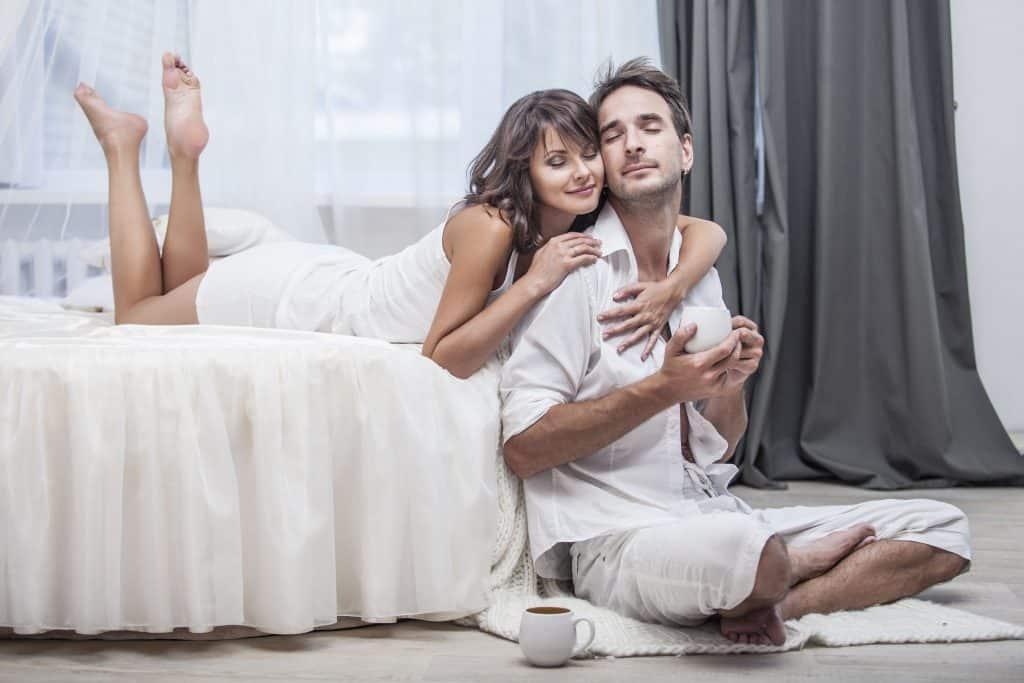 Casal abraçado, curtindo um momento relaxante em quarto.