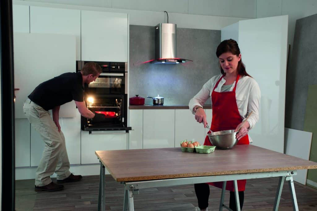 Imagem mostra um homem e uma mulher na cozinha, ele retirando um prato do forno elétrico de embutir e ela preparando um alimento.