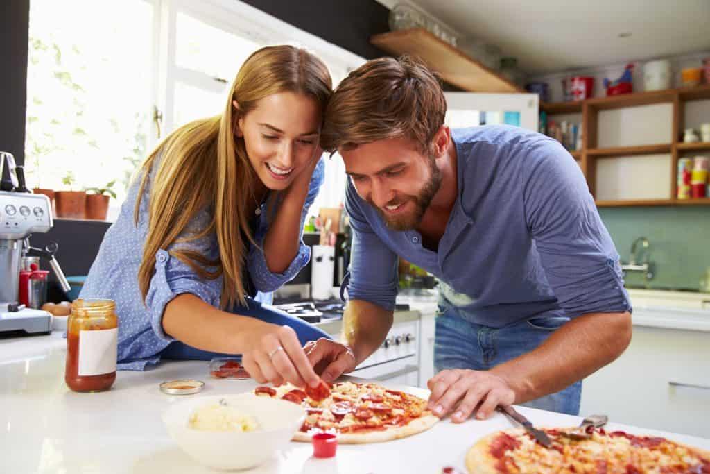 Imagem de casal preparando pizza.