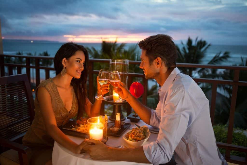 Imagem de um casal jantando a luz de velas.