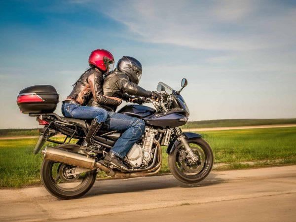 Casal de motociclista conduzindo uma moto com baú traseiro.