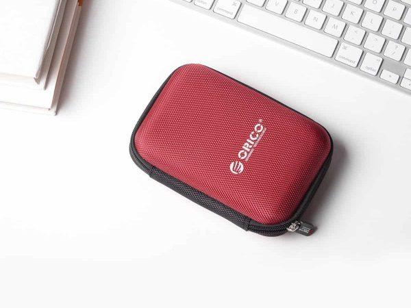 Imagem mostra um case de hd externo ao lado de um teclado de computador.