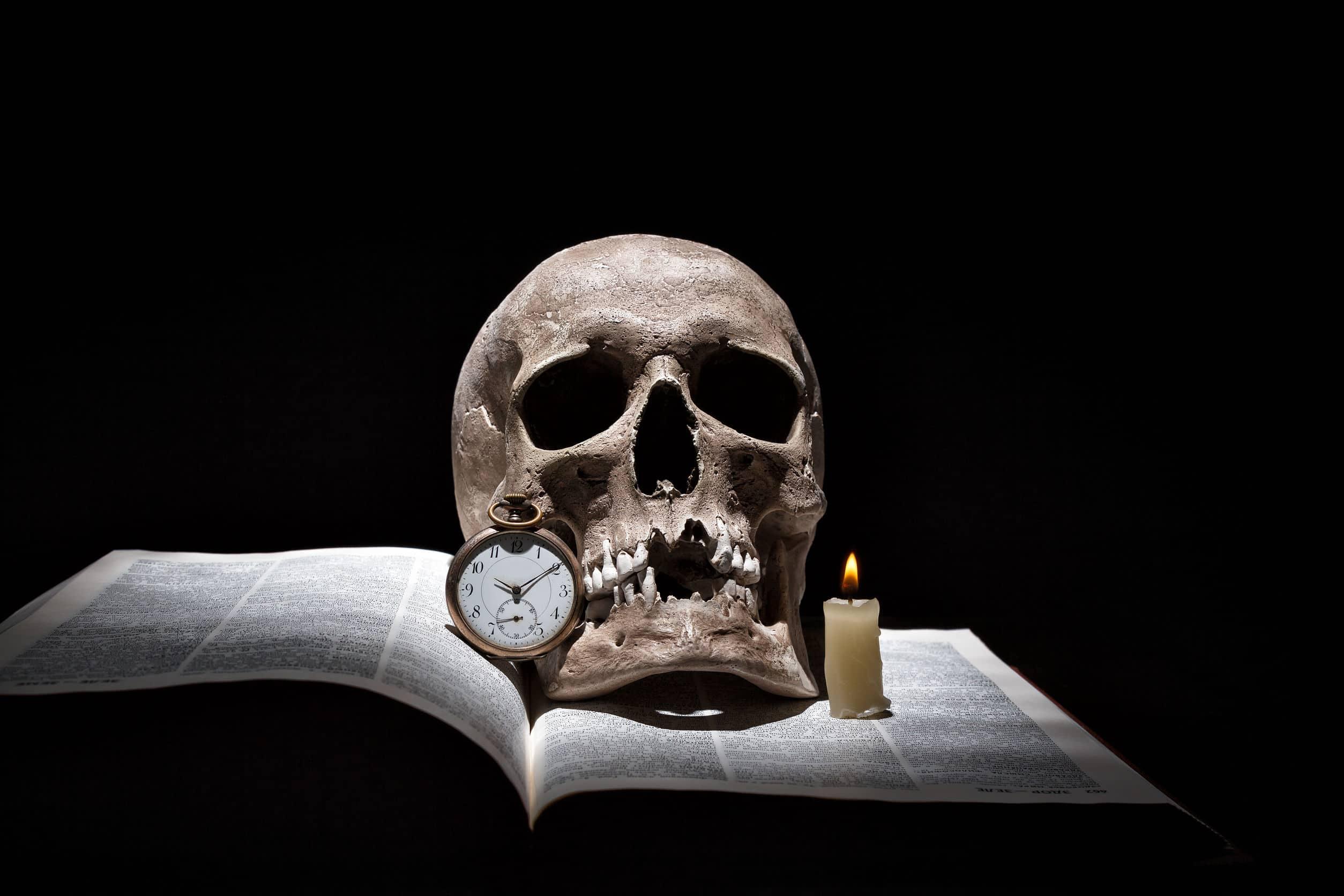 Imagem mostra um livro aberto sob uma caveira, uma vela acesa e um relógio.
