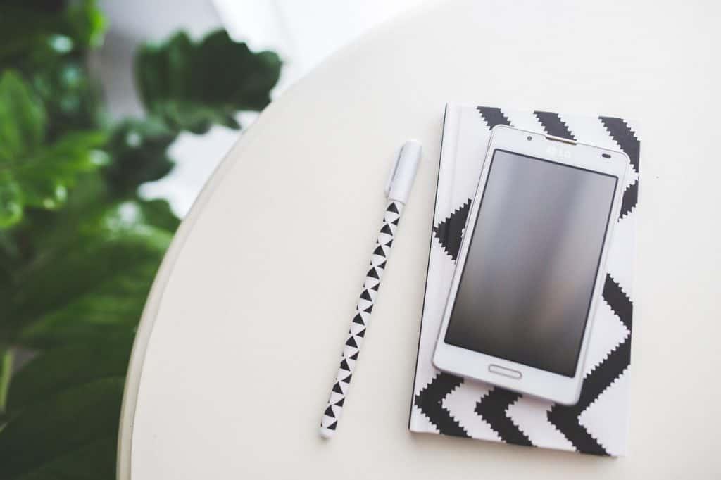 Na foto um celular em cima de um caderno ao lado de uma caneta em cima de uma mesa branca.