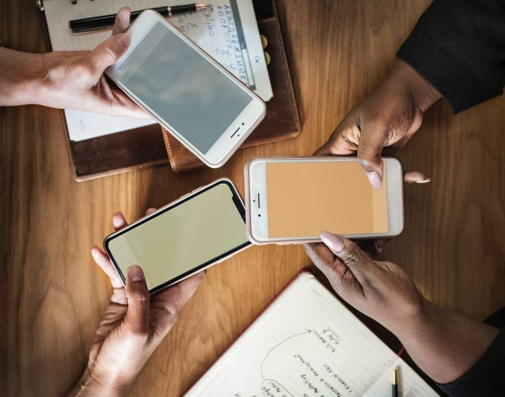 Na foto três pessoas segurando seus celulares em cima de uma mesa.