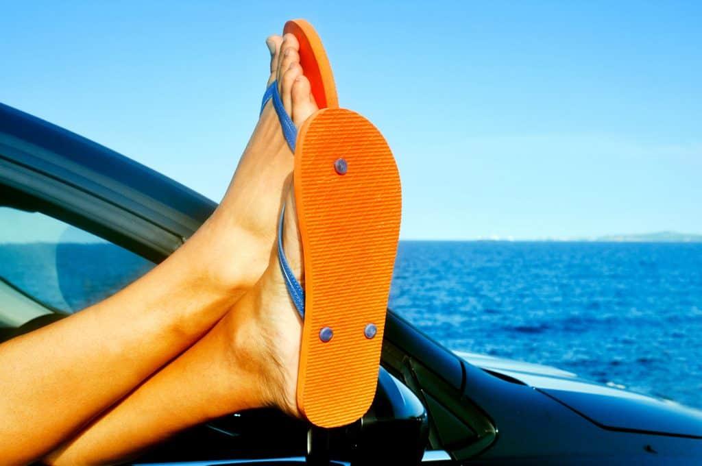 Homem com os pés na janela do carro usando havaianas.