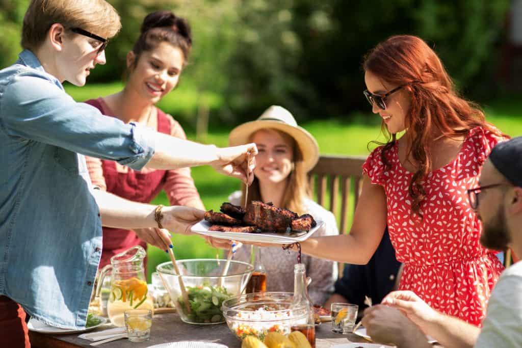 Rapaz serve churrasco a grupo de pessoas em torno de uma mesa ao ar livre.