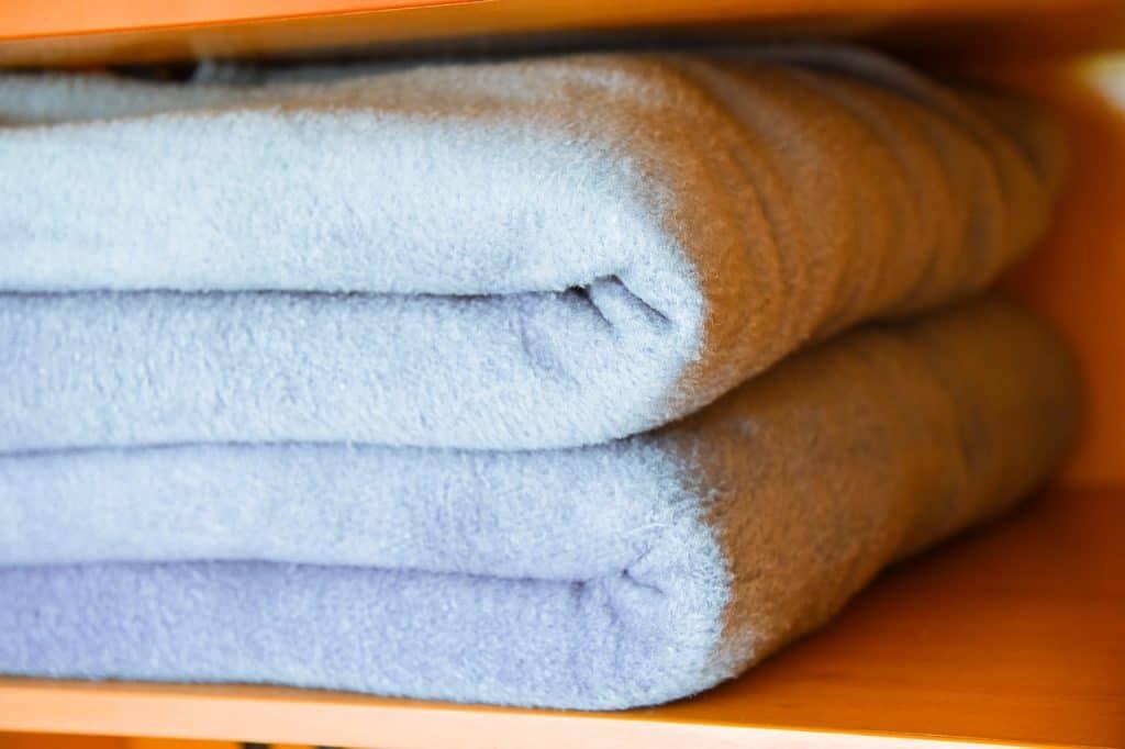 Imagem de cobertores de microfibra azuis guardados em um armário