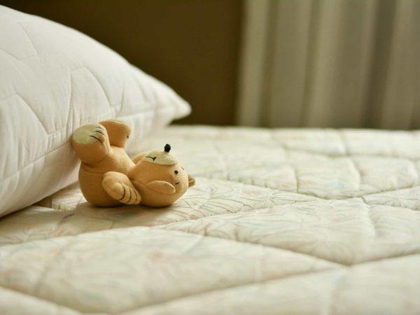 Foco em um colchão e travesseiro, sem roupa de cama. Um ursinho de pelúcio pequeno está em cima do colchão.
