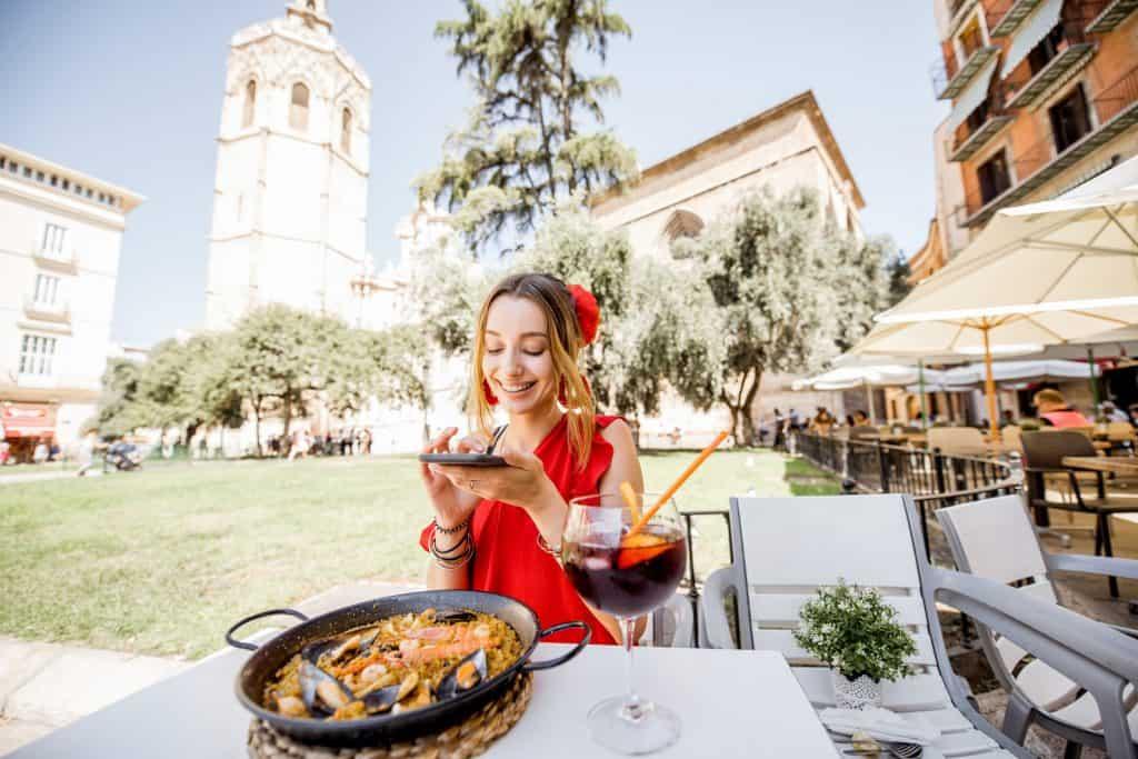 Imagem de mulher em restaurante tirando foto do prato de paella.