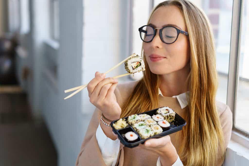 Mulher segurando uma pequena bandeja de sushi e manuseando o hashi com a outra mão.