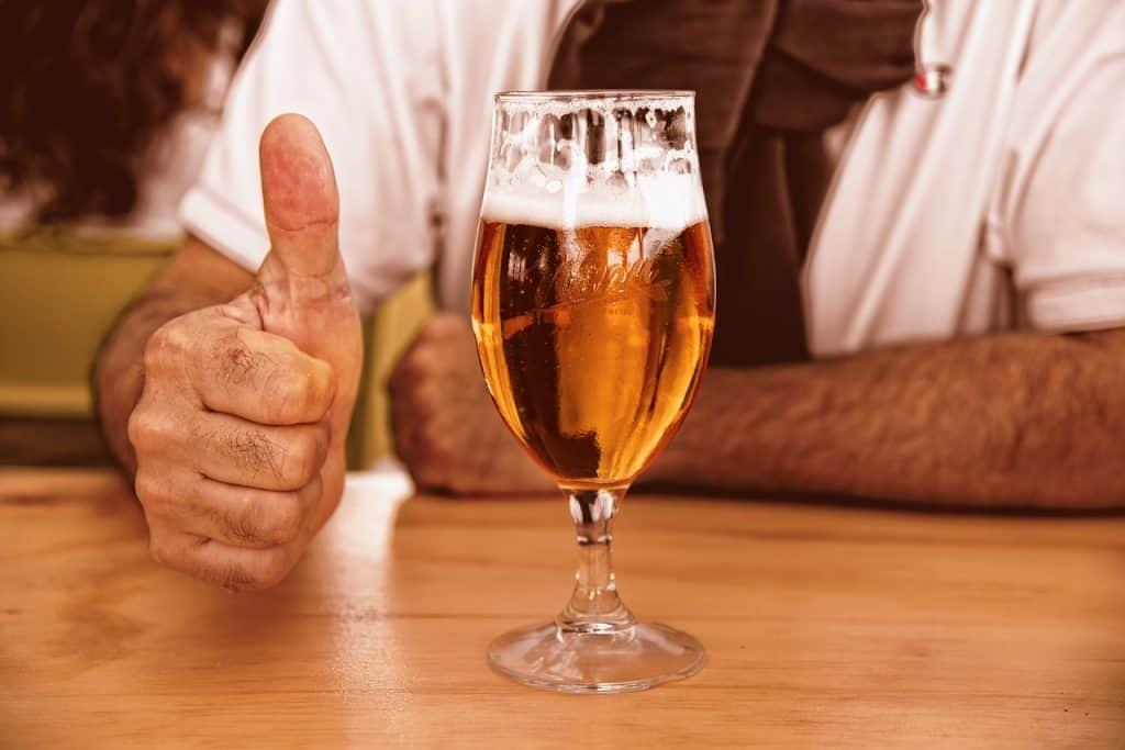 Imagem mostra um copo de cerveja à frente de um homem que faz sinal de positivo.