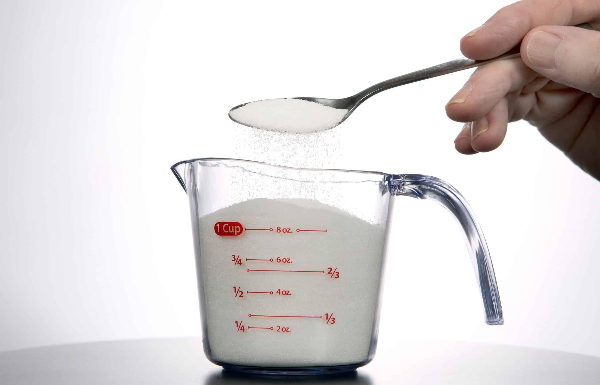 Na foto se visualiza a mão de um homem colocando ingrediente branco em um copo medidor localizado em cima de uma mesa.