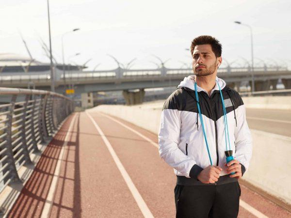 Imagem mostra um homem usando uma corta vento em uma pista de atletismo.