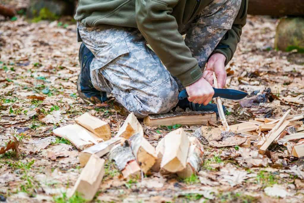 Um homem cortando pedaços de madeira no meio da mata com uma faca de caça.